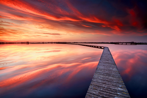 red clouds with path over water